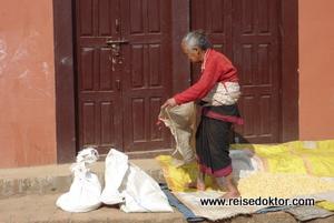 Nepal: Frau beim Maistrocknen